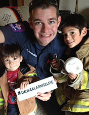 Firefighter with kids holding #smokealarmselfie sign